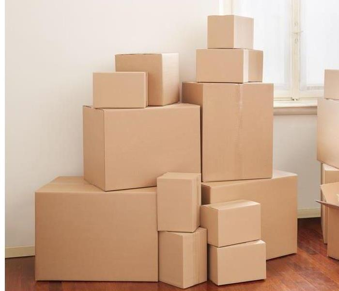small and big plain brown moving boxes stacked up on top of each other on top of a wooden floor next to a window