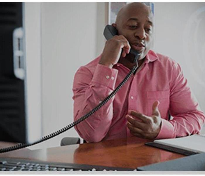 gentleman with a pink shirt talking on the phone on his desk