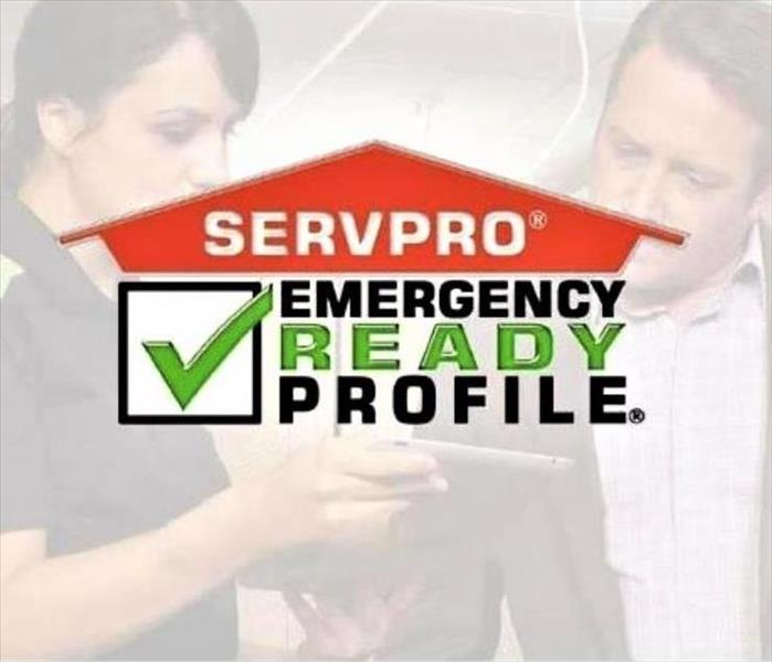 a female technician and male customer in the background with servpro logo with a green check mark in a box