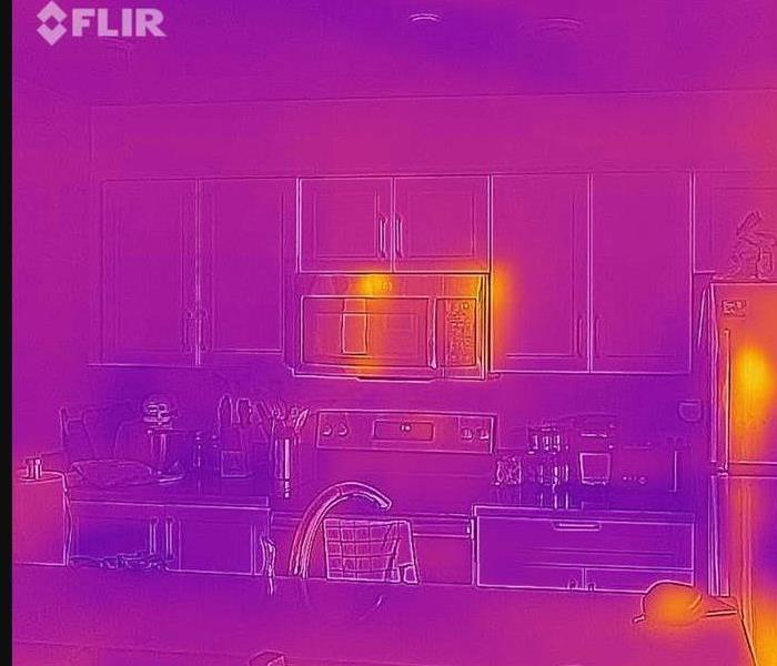 orange and purple hue picture of a kitchen through an infrared camera